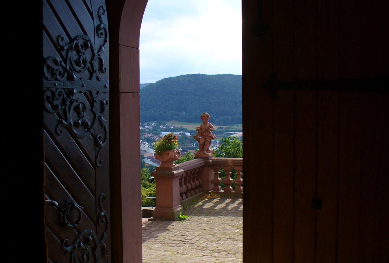 """Blick aus der Kirchentür vom Kloster Engelberg bei Miltenberg - zu sehen ist ein Engel auf der Brüstung - Blick geht weiter ins Maintal - Das Bild illustriert den Wusch """"Lass dich auf Händen tragen""""!"""