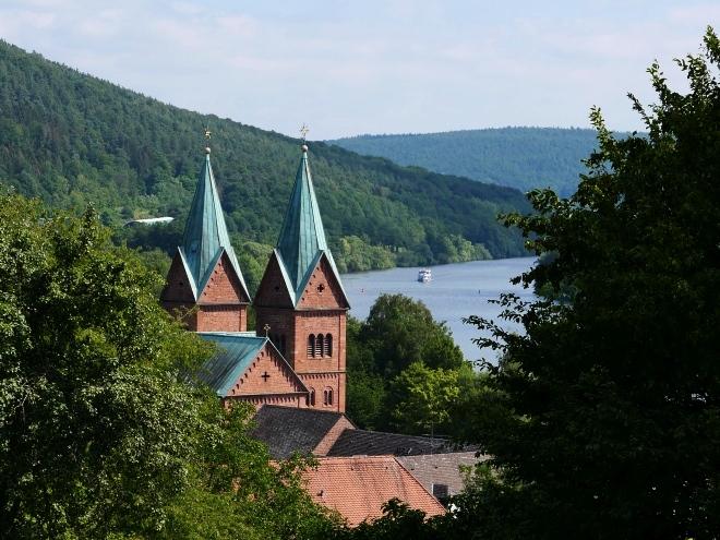 Blick auf Kloster Neustadt und den Main mit Schiff. Wer die Schiffe, vorbeigleiten sieht, spürt sie: Die Feier der Gemächlichkeit.